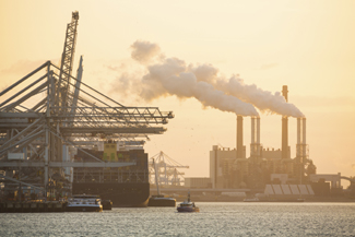 A photograph of gantry cranes and a ship with air emissions from smoke stacks in the background.