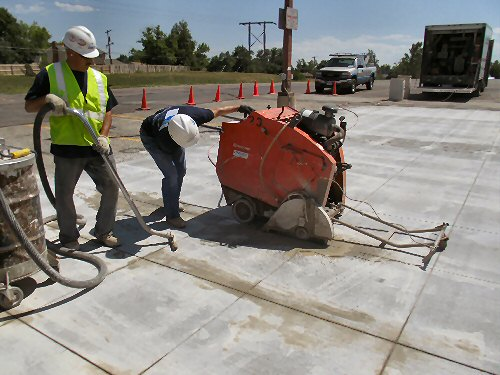 Construction workers install slotted concrete to form a pervious pavement for stormwater runoff.