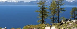 Bicyclist with view of Lake Tahoe's blue waters and snowcapped mountains.