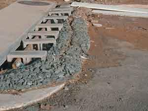 cinder blocks and gravel keeping sediments out of storm waterdrain
