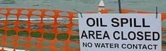 Picture of a sign that indicates that the area is closed due to an oil spill on the water.