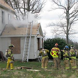 Firefighters stand outside a house being used for fire training