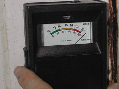 Moisture meter, showing high moisture content in gypsum board behind tile.