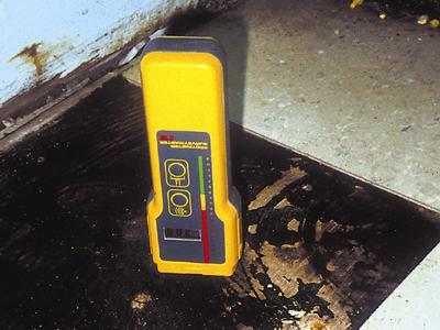 Measuring moisture levels of a subfloor.