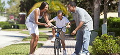 image of parents teaching children how to ride a bike
