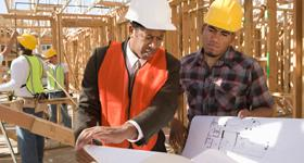 Two workers consulting blue prints while standing inside the frame of a new house.