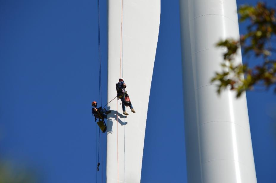 Air Force personnel inspecting the wind turbine blades
