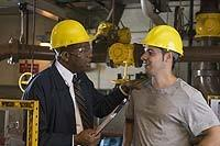 This is a picture of two men in hard hats in an industrial plant