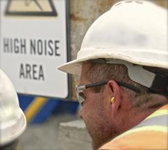 "A photograph of a man wearing a hard hat with ear protection with a sign saying ""High Noise Area"" in the background."