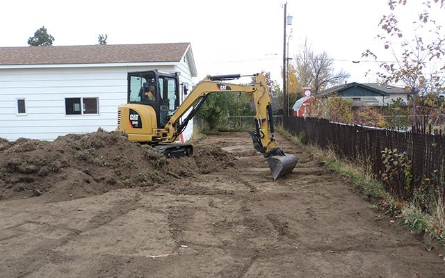 Image of construction vehicle cleaning up residential yard