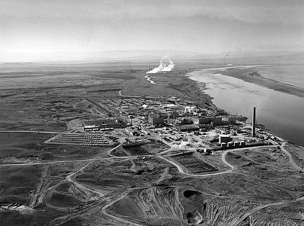 N reactor shown in the foreground with the KE and KW reactors in the background along the Columbia River circa 1960. B Reactor is shown in the distance.