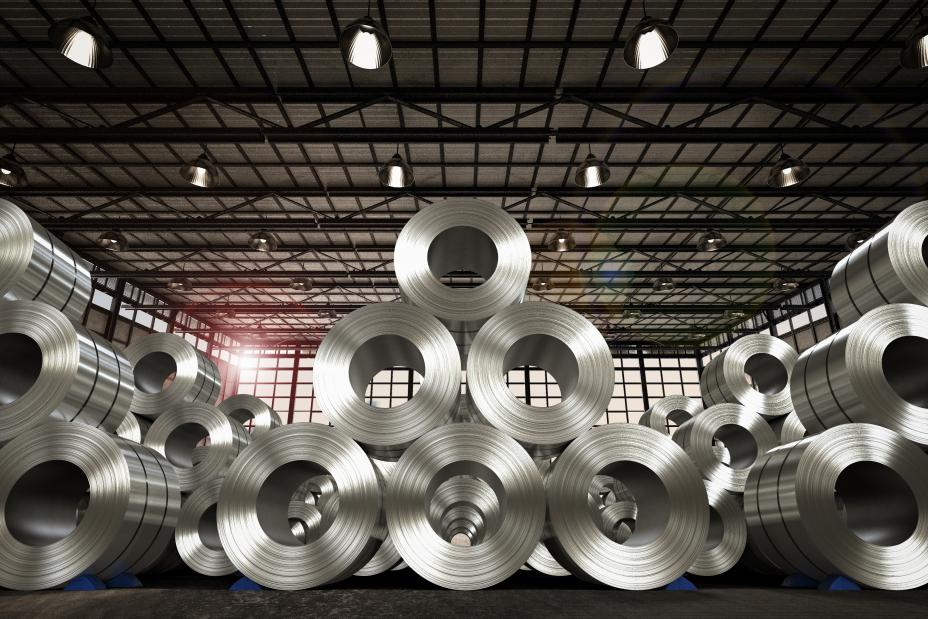 This is a picture of a roll of steel sheets in a well-lit, clean factory. There are many stacks, each stack in the shape of a pyramid, with three rows on the bottom, two in the middle and one on top.