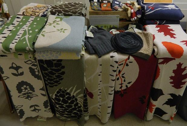 This is a picture of a textiles on a table. There's a wide variety of textiles and colors, including socks, winter hats, and drapes and curtains.