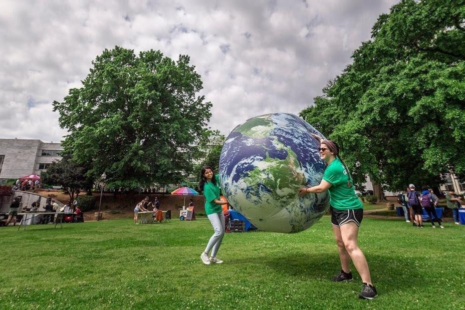 This is a picture of two women in green t-shirts holding an inflatable ball of the earth. They're outside on grass. Trees with green leaves and a cloudy sky are in the background.