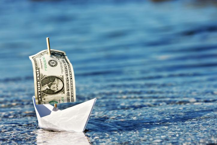 Paper boat with dollar bill for a sail