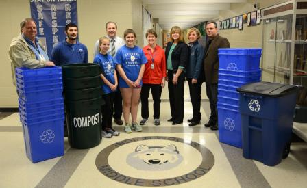 This is a picture of nine people standing around numerous recycling and composting bins.