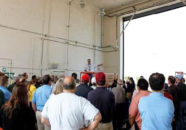 collection of people touring a large storage space at a federal facility