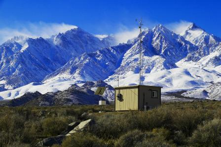 Small building with radio antenna on valley floor with snowcapped peaks in background.