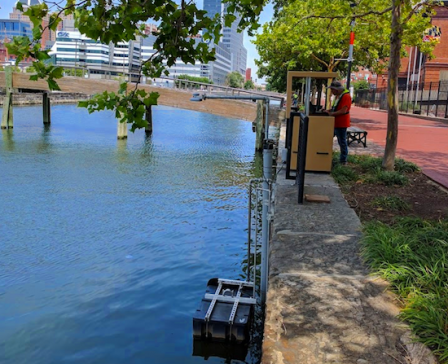 Village Blue's water quality sensors are mounted underwater in Baltimore's Jones Falls River, shown here. The data collected by the sensors is stored and transmitted by equipment housed in this weather-proof box (foreground).
