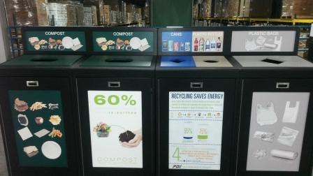 This is a picture of four different compost and recycling bins lined in a row, adjacent to each other. Each are labeled with words and pictures. From left to right, there are two compost bins, a bin for cans and plastic bottles, and one for plastic bags.
