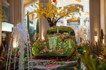 This is a picture of artwork that that resembles nature. There's a tree with yellow foliage in the background, a small water fountain in the foreground, plants all around, and an old-fashioned car covered with grass and leaves in the center.