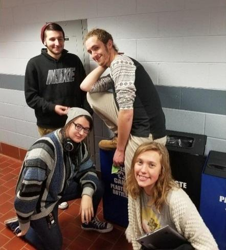 This is a picture of four Raritan Valley College students posing for the camera in front of various recycling bins inside a building.