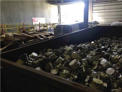 This is a picture of recycling materials inside a large, brown container inside a warehouse.