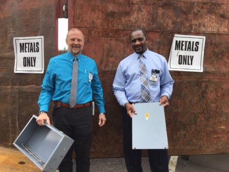 "This is a picture of two men holding items in front of a bin that has two signs that read ""METALS ONLY."""