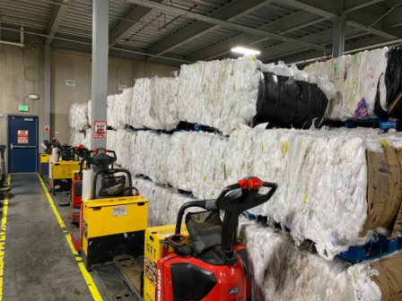 This photo shows what appears to be stacked rows of recyclable bundles. Unoperated fork lifts are on the ground next to the piles.