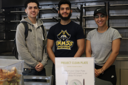 "This is a photo of three UMASS Dartmouth students posing in front of a ""Project Clean Plate"" poster. Project Clean Plate is UMASS Dartmouth food recovery initiative."