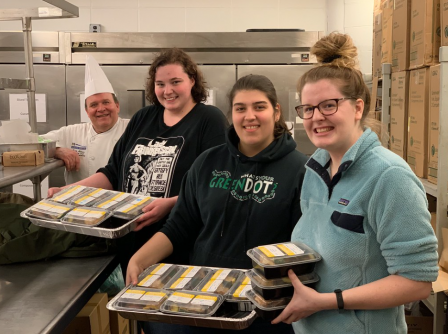 This is a photo of three UMASS Dartmouth students posing with a university chef in a facility kitchen. The students are holding food.