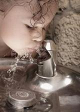 child drinking from fountain
